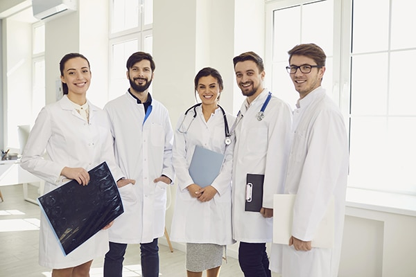 Group of doctors standing and smiling while facing the camera
